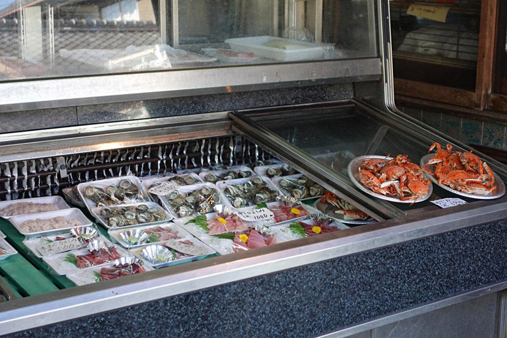 魚屋さんのショーケースに並ぶ色とりどりの魚とカニ