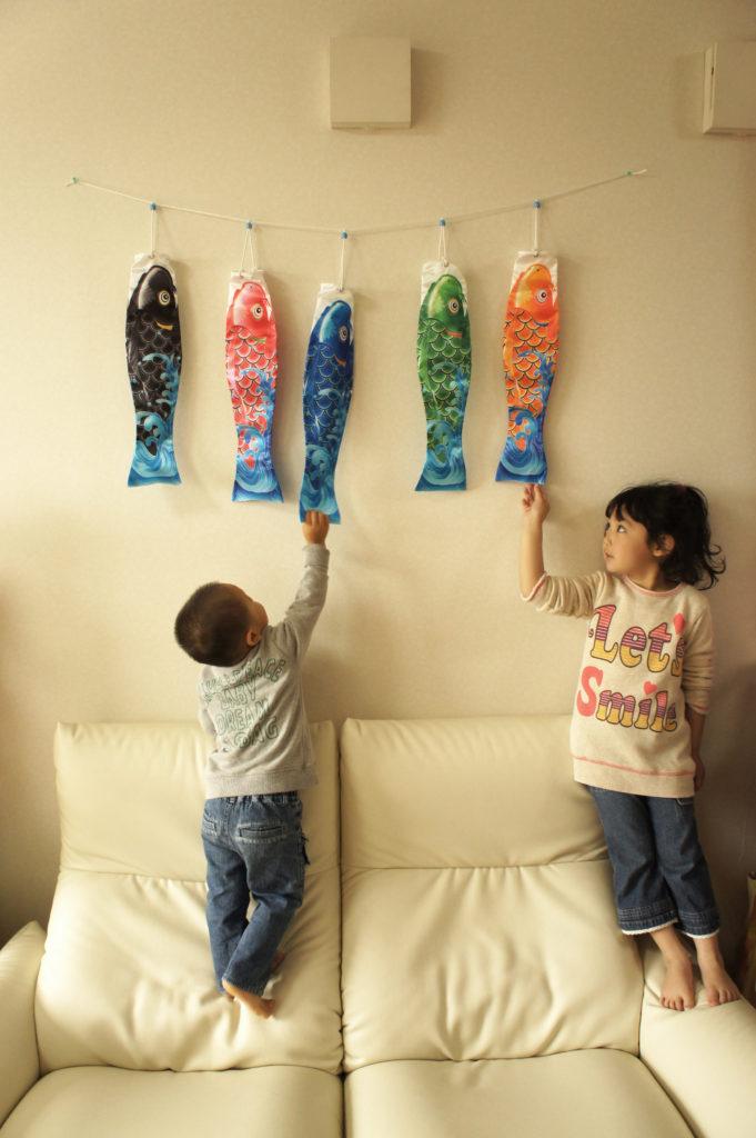 部屋に飾った鯉のぼりとそれを見る子供