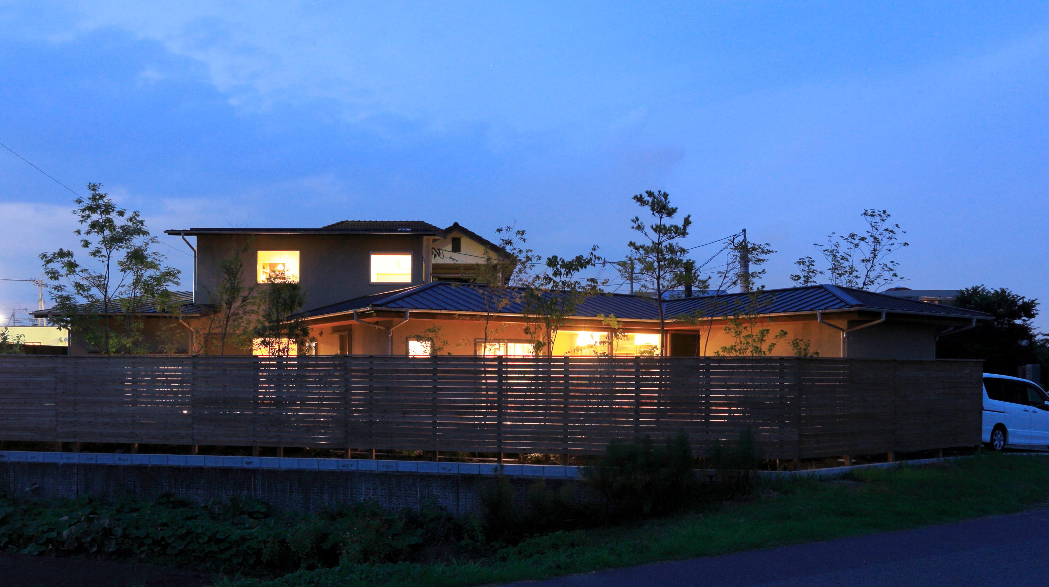 夕方に部屋の明かりが漏れ美しい外観の家