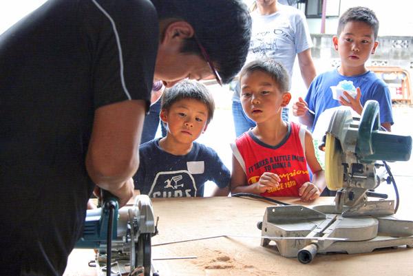 大工さんの手仕事を見学する子供達