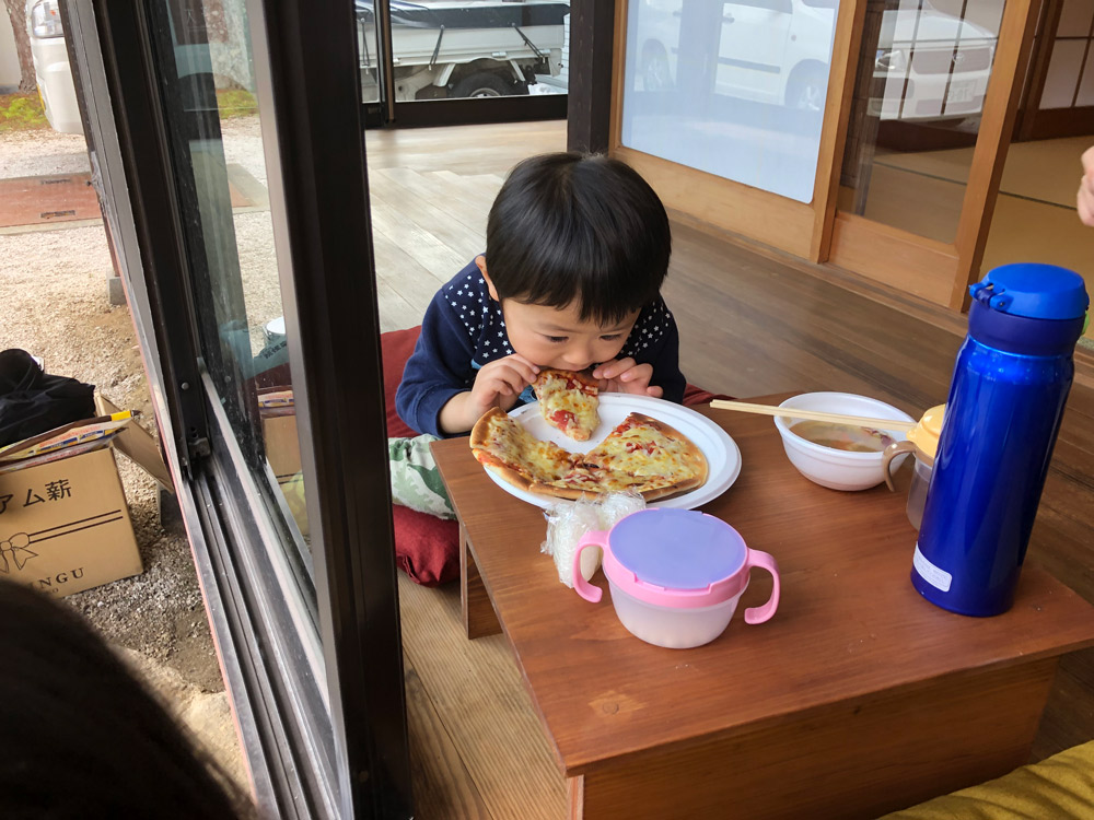 手作りピザを食べる子供