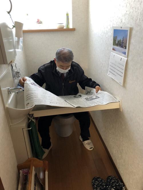 トイレの作りつけ読書棚で新聞を読む